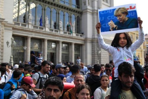 A girl holds up a poster of Angela Merkel.
