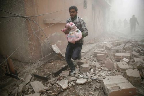 Man carries baby through Syrian rubble