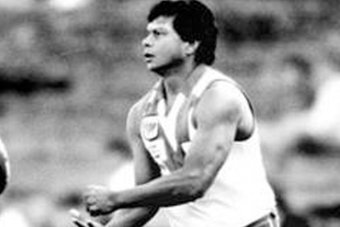Northern Territory-born football star Maurice Rioli handballs during a game.