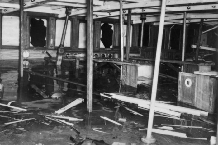 Interior of the top deck of the HMAS Kuttabul showing splintered wood and damaged windows.