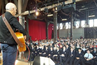 A view from the stage as Paul Kelly performs for a large audience of school students.