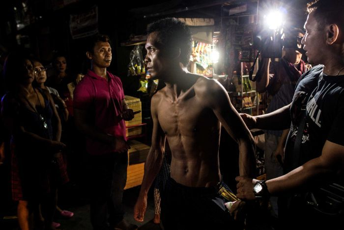 A half naked man detained by policemen in Manilla