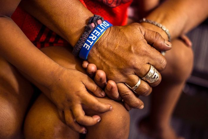 A woman wearing a Duterte wristband accompanies her son at a police station after being detained for violating a curfew.