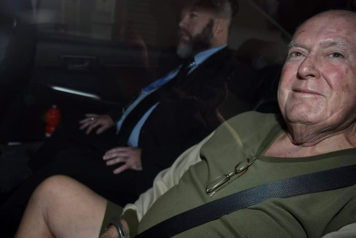 ohn Chardon in the back of a police car being brought into the police watch-house in Brisbane.