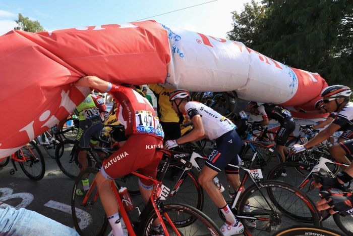 Bikers pass under deflated arch at Tour de France
