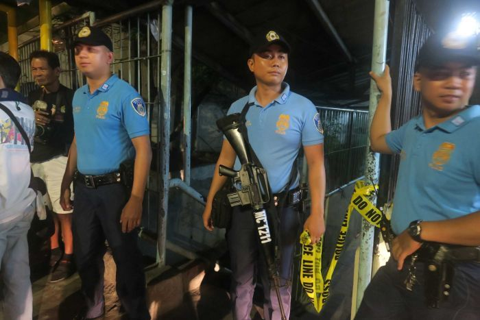 Police secure a crime scene where a drug runner was killed in Marikina City, Philippines