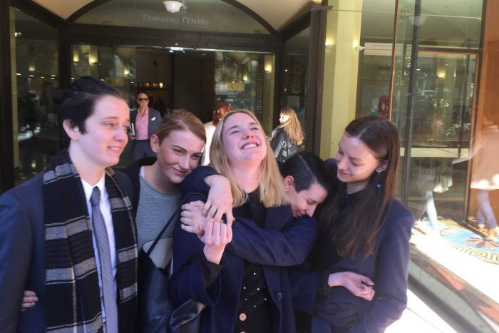 Paloma Brierly Newtown surrounded by four friends laughing and looking elated.