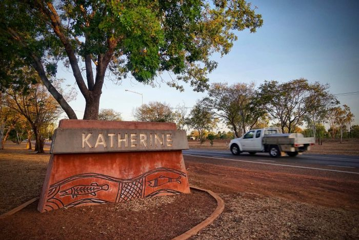 A car drives down a road. On the roadside is a sign saying Katherine.