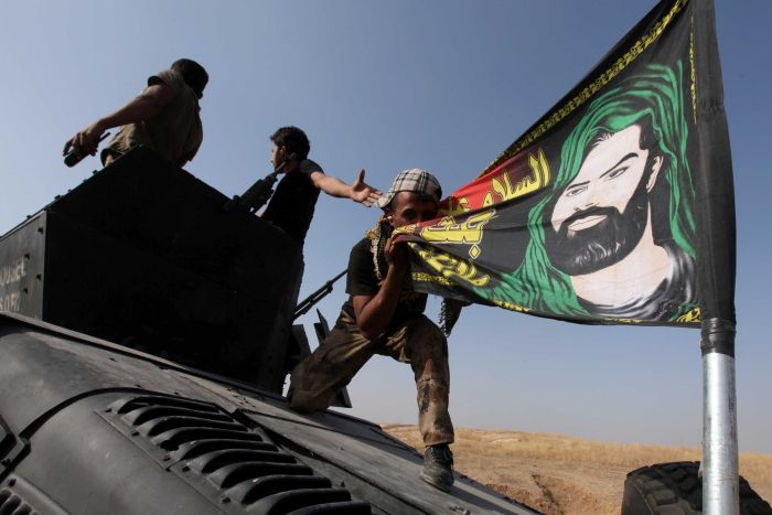 A member of the Iraqi Special Operations Forces (ISOF) kisses a shiite flag on the top of a military vehicle on the outskirts of Bartila, east of Mosul, during an operation to attack Islamic State militants in Mosul