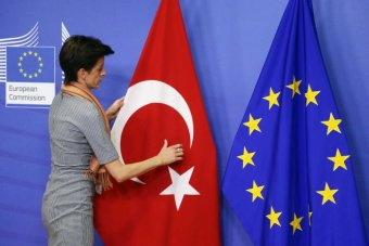 A woman adjusts the Turkish flag next to the European Union flag.