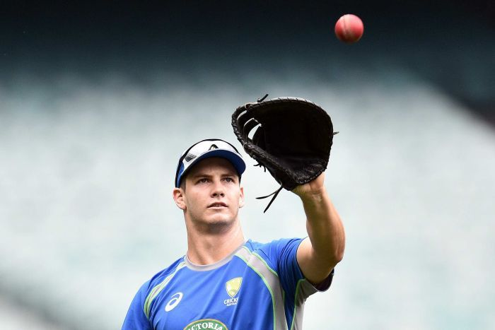 A mid shot showing Hilton Cartwright preparing to catch a cricket ball with a baseball glove.