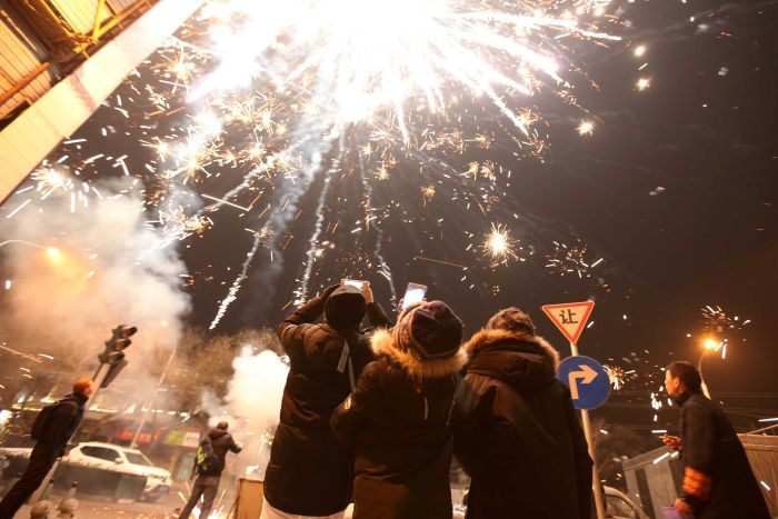 People watch fireworks explode on the streets of Beijing.