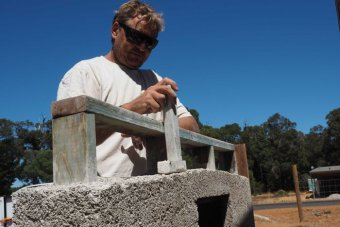 BuilderGary Rogers demonstrates tamping the hemp into place