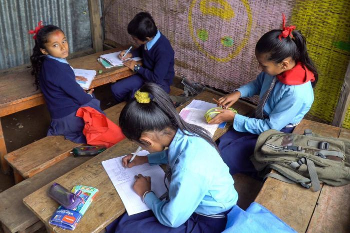 Students studying in a temporary classroom.
