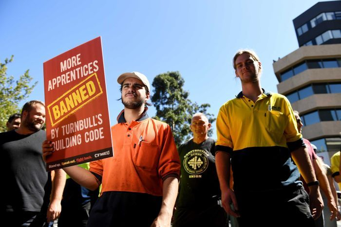 A man holds a sign that says 'More apprentices banned by Turnbull's building code'.