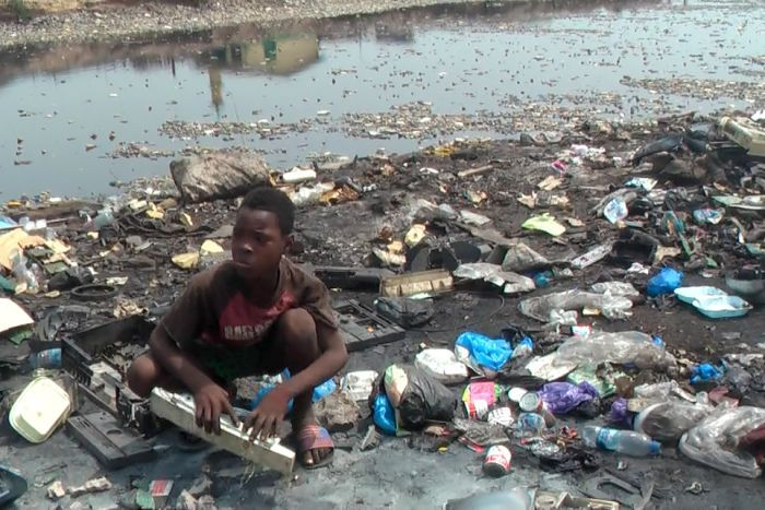 Boy crouches amongst e-waste at Agbogbloshie dump in Ghana.