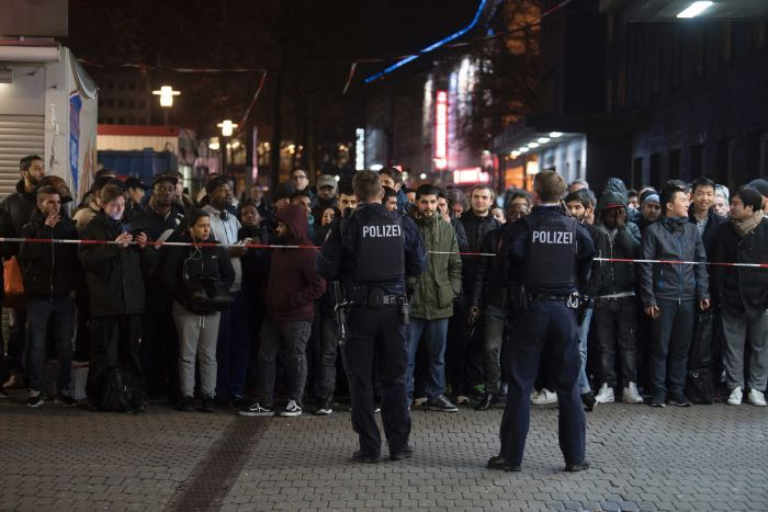 Travellers and bystanders are cordoned off by police outside the Dusseldorf main station.