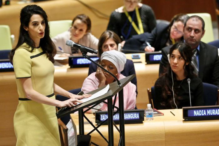 Amal Clooney speaks at podium as other people listen.