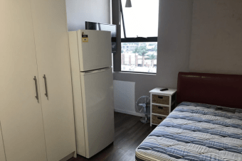 A fridge, cupboard and bed inside a micro apartment in Sydney