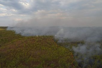 Red snaking line of fire and smoke billow up from tree lined hills in far north Queensland savanna country
