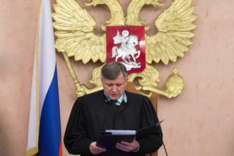 Russia's Supreme Court judge Yuri Ivanenko reads the decision in a court room.