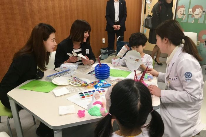 Karen Pence listens to a child who is painting a mask as part of an art therapy session in seoul