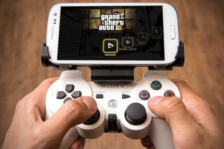 An adapter clips a PlayStation 3 controller onto an Android phone.