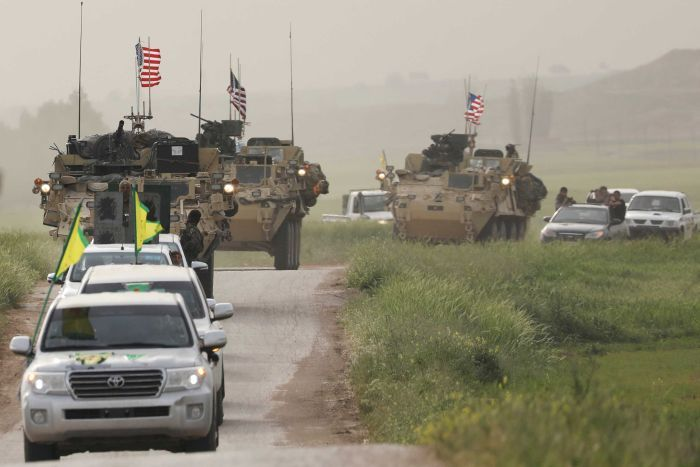 Kurdish fighters from the People's Protection Units (YPG) head a convoy of US military vehicles.