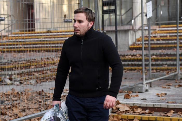 Adam Cranston leaving the Sydney Police Centre in Surry Hills, wearing all black and carrying papers in his right hand