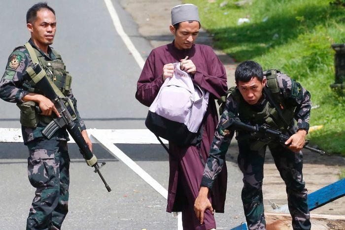Government troops frisk a Muslim man at a checkpoint leading to Marawi city.