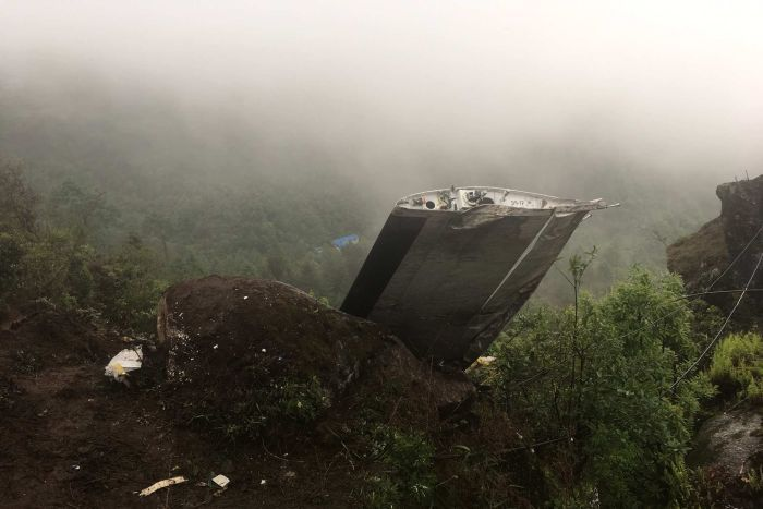 A wrecked plane wing is seen in mountainous terrain.