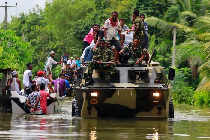 Sri Lankan soldiers drive large military vehicles through floodwaters to evacuate victims, a boat of people paddles next to one.