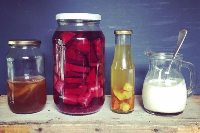 Jars of food waste that are being turned into fermented drink tonics sit on a wooden board.