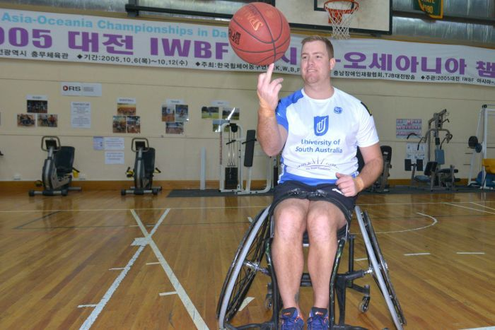 A man in a wheelchair spinning a basketball on his finger