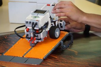 A Lego robot sits at the top of a ramp.