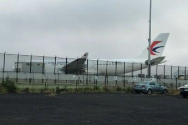 A China Eastern plane sitting on the tarmac at Sydney Airport after turning back because of a large hole in an engine.