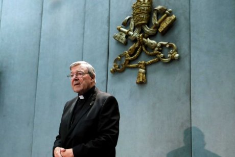 George Pell stands before a microphone, hands crossed over each other.