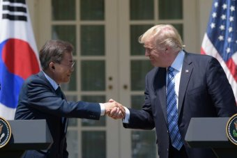 President Donald Trump and South Korean President Moon Jae-in smile as they shake hands at a White House podium.