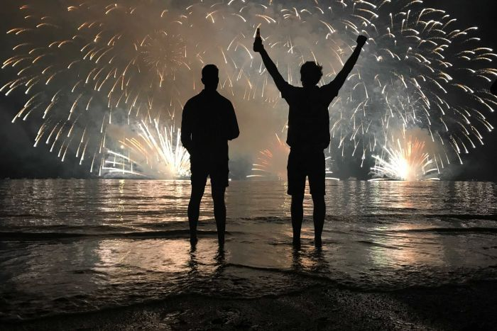 Two men in silhouette watch fireworks explode over Darwin
