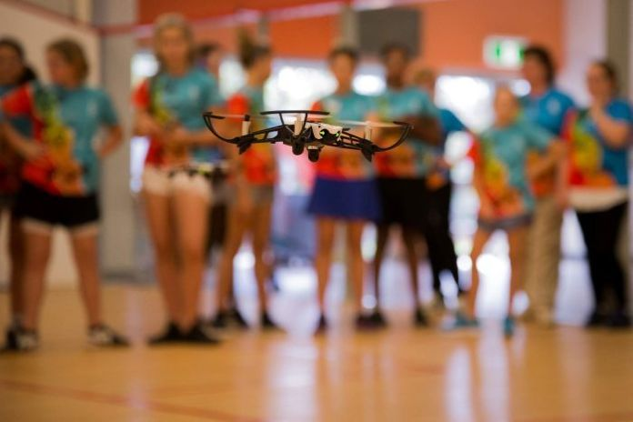 A small drone hovers in mid air as a crowd of girls aged between 10 and 17 look on in the background.