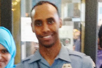 Police officer Mohamed Noor stands in uniform smiling into the camera.