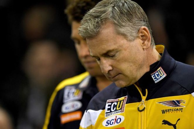 A tight head and shoulders shot of Adam Simpson with his eyes closed and his head bowed wearing an Eagles jacket.