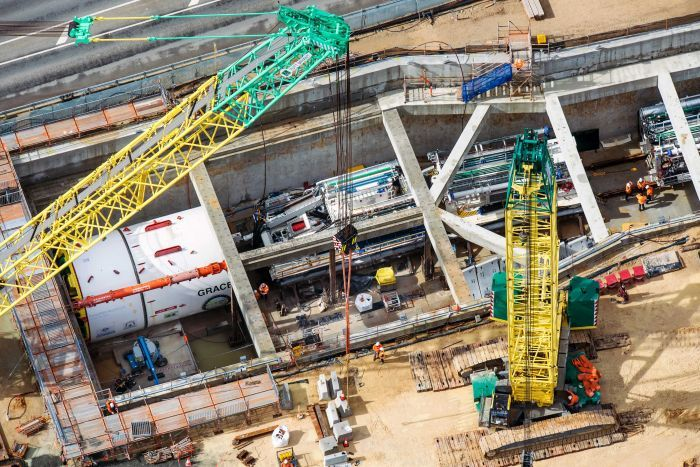 The tunnel boring machine in place, surrounded by concrete housing, workers and other equipment.