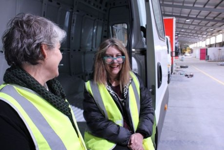 Two women, Sally Goldstraw and Elizabeth Jewson from WRISC in Ballarat, sit next to a van.