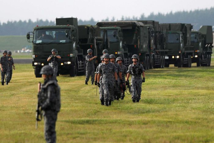 Soldiers in a green field walk towards the camera with heavy military machinery in the background.