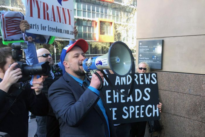 """The UPF's Neil Erikson yells into a megaphone while holding a """"Dan Andrews beheads free speech"""" sign outside court."""