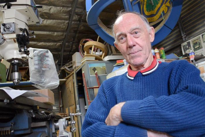 An older man with thin grey hair sits in a workshop, surrounded by machinery and cut outs of round sundials stacked to the roof.