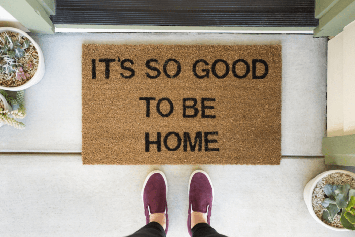 "A person stands in front of a welcome mat that says ""it's so good to be home""."