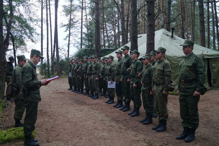 Soldiers from Belarus line up to hear an order, which begins the drills. They are at a forested training ground in Belarus.