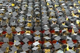 Students wearing mortarboards and gowns seen from above at a university graduation ceremony